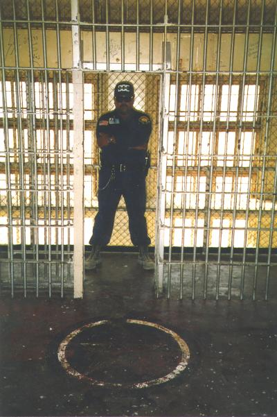 Guard in front of painted pentagram, 1985-2008, Department of Corrections, McNeil Island Corrections Center Photograph Collection, 1855-2010, Digital Archives.